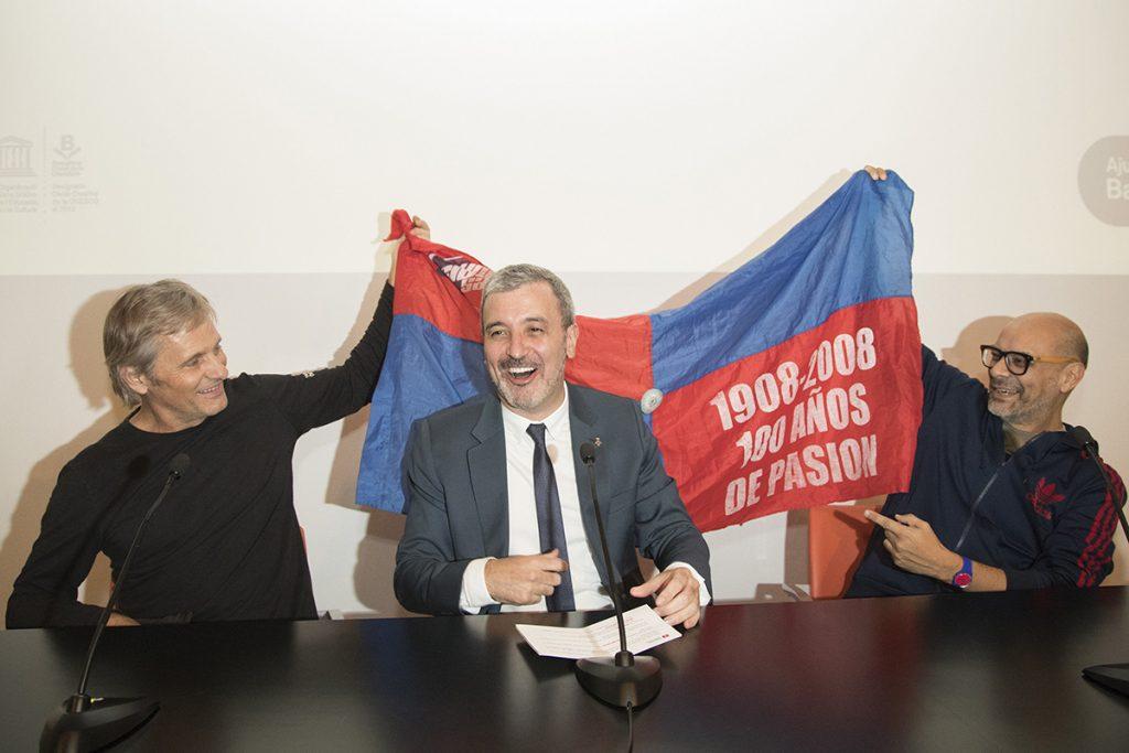 FOTO EFE. Mortensen y el poeta Fabián Casas muestran la bandera del club argentino al alcalde de Cultura de Barcelona, Jaume Collboni