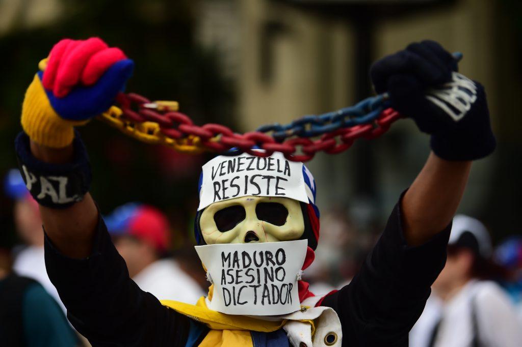 En Venezuela, oculta bajo un puente, la joven voluntaria mueve las manos a toda prisa para entablillar el tobillo ensangrentado de un fotógrafo