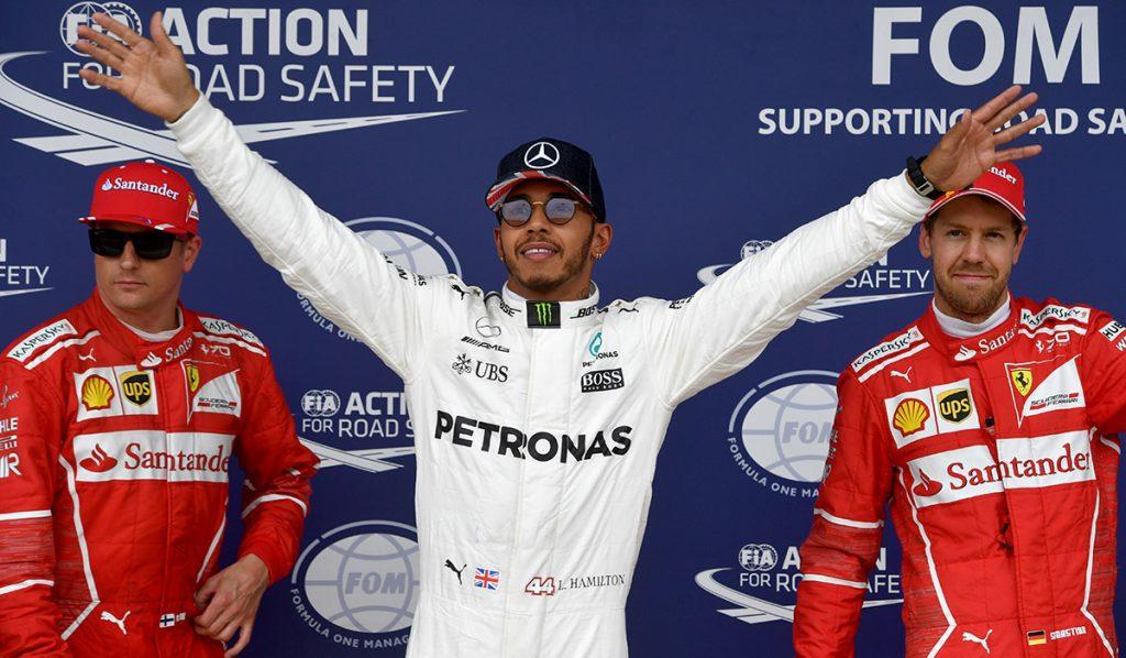 FOTO AFP. Hamilton flanqueado por los pilotos de Ferrari.