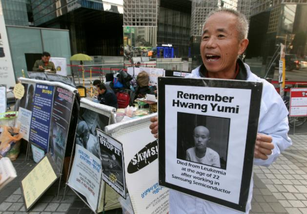 Foto de Hwang Sang-gi, fundador de la asociación Banolim, muestra una fotografía de su hija Yu-min, que murió de leucemía; el hombre se manifiesta a las afueras de la fábrica de Samsung. @Ap