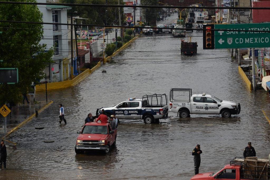 SAN MATEO ATENCO, ESTADO DE MÉXICO, 28AGOSTO2017.- Debido a las fuertes lluvias que se han registrado en las últimas horas en el Valle de Toluca, la entrada principal de San Mateo Atenco se inundó, por lo que elementos de la CESC auxiliaron a la población para poder atravesar la zona inundada.  FOTO: ARTEMIO GUERRA BAZ / CUARTOSCURO.COM