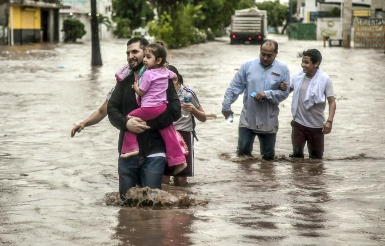 La gente en medio de la inundación  en una calle de  Culiacán de Sinaloa, AFP RASHIDE FRIAS