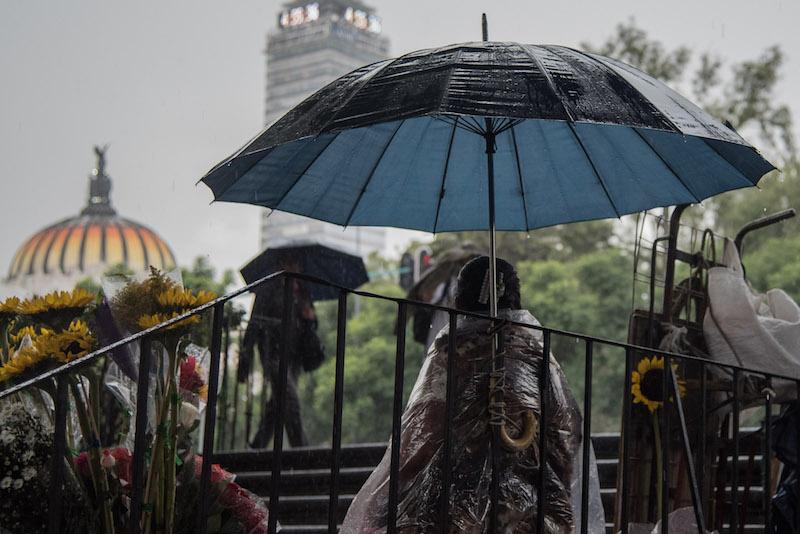 Una persona comerciante se refugia de la lluvia en unas escaleras cercanas al metro Hidalgo. Se registra lluvia moderada  esta tarde en la capital sobre la avenida Hidalgo en el centro histórico.  FOTO: MARIO JASSO / CUARTOSCURO.COM