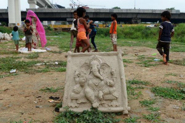 Niños indios juegan cerca de la deidad india con cabeza de elefante  Ganesha en Nueva Delhi. FOTO: AFP