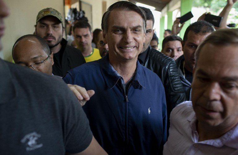 El candidato presidencial de derecha de Brasil para el Partido Social Liberal (PSL), Jair Bolsonaro (C), se retira luego de emitir su voto durante las elecciones generales, en Río de Janeiro, Brasil, el 7 de octubre de 2018. Foto: AFP /Mauro Pimentel