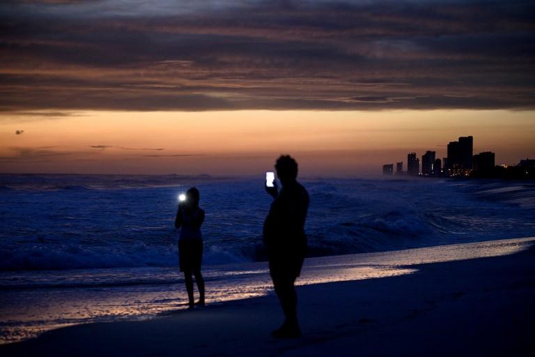 La gente visita la playa mientras espera el huracán Michael en la Florida. / AFP PHOTO / Brendan Smialowski