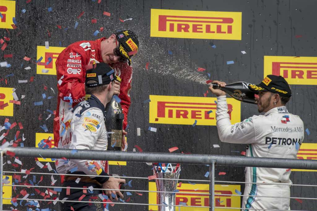 Oct 21, 2018; Austin, TX, USA; Ferrari driver Kimi Raikkonen (center) of Finland celebrates winning the United States Grand Prix at Circuit of the Americas with Red Bull Racing driver Max Verstappen (left) of Netherlands and Mercedes driver Lewis Hamilton (right) of Great Britain. Mandatory Credit: Jerome Miron-USA TODAY Sports