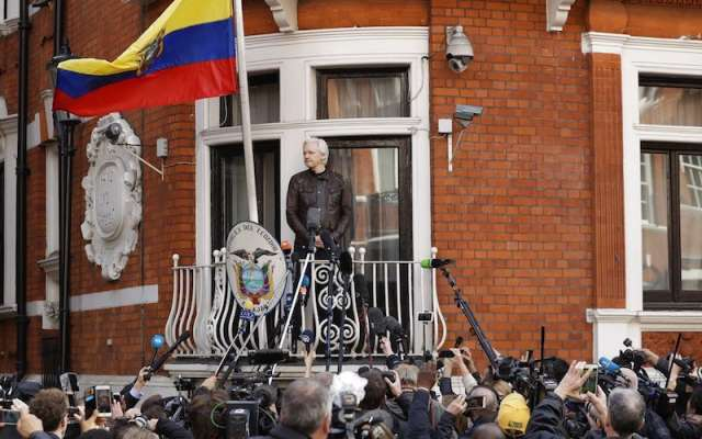 Julian Assange mira desde el balcón de la embajada ecuatoriana antes de hablar en Londres.  Foto: AP
