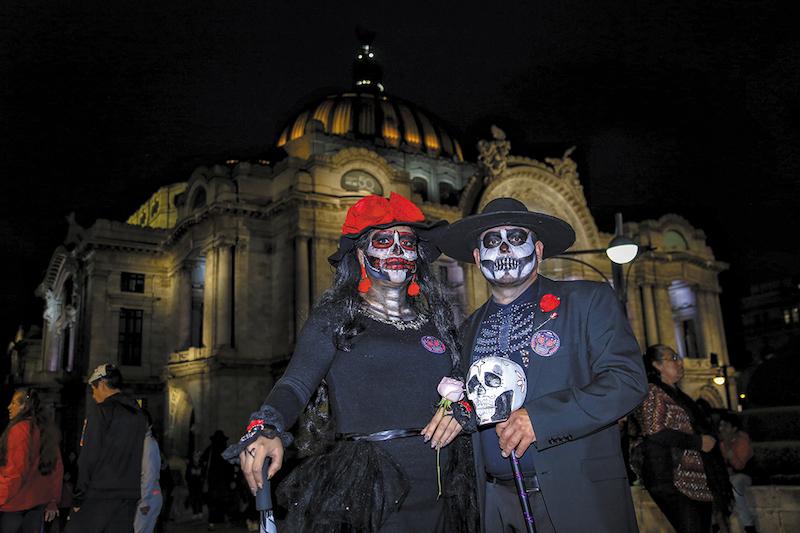 Una pareja de asistentes muestra el elaborado trabajo de su maquillaje y vestimenta. Foto: Nayeli Cruz / Heraldo de México.