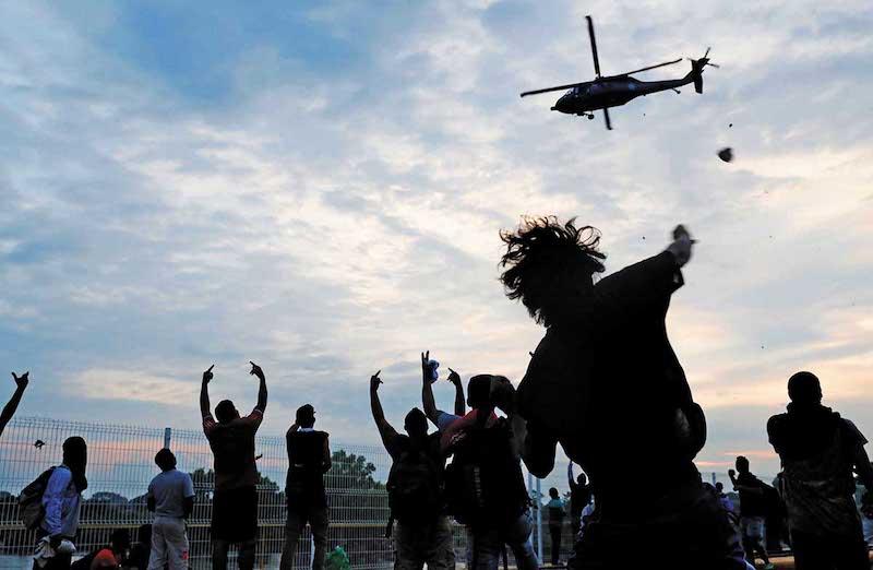 Las señales que hacían con las manos hace suponer a expertos que los agresores que acompañan la caravana son maras.  Foto: Reuters