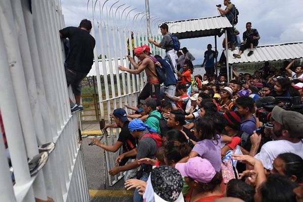 Cientos de migrantes centroamericanos derribaron una puerta del puente internacional Rodolfo Robles, pero policías federales les impidieron el acceso masivo con el que pretendían ingresar a territorio mexicano. Foto: AFP