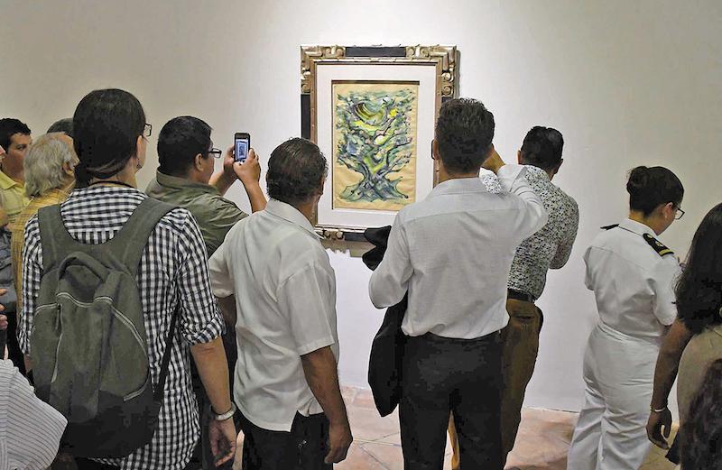 Visitantes observan fotografías de la muestra