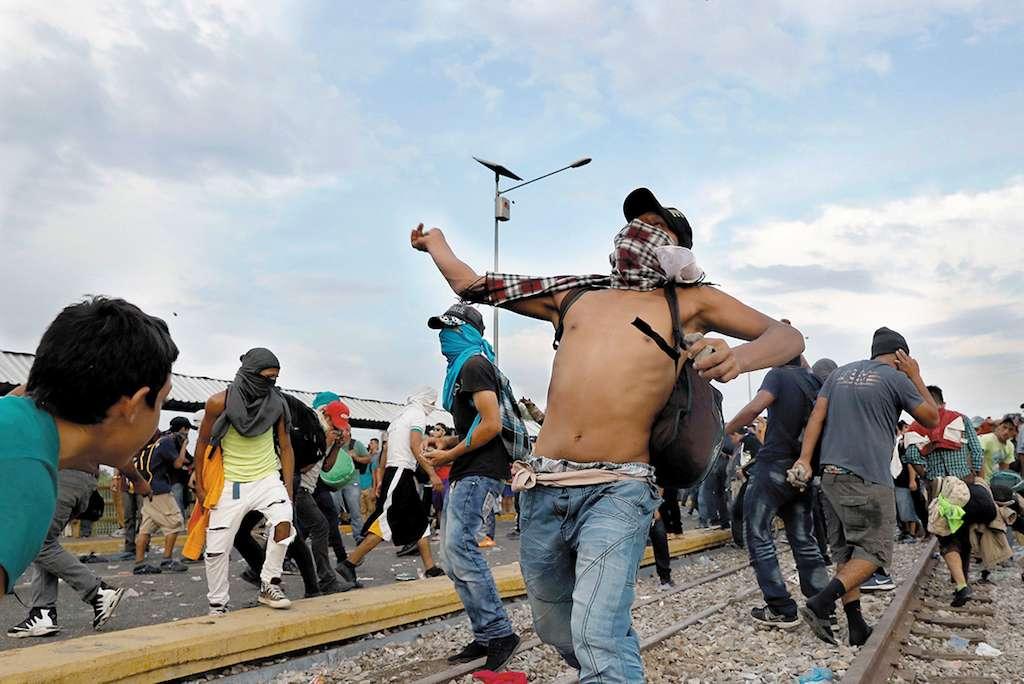 Los migrantes centroamericanos lanzaban piedras y petardos, en el puente fronterizo. REUTERS/Carlos Garcia Rawlins