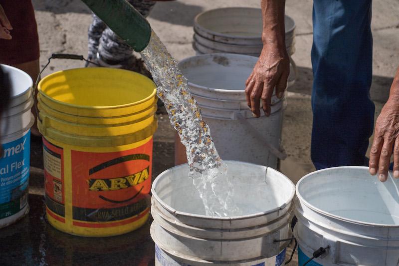 Habitantes  recolectaron agua en cubetas tras el paso de una pipa que repartió el liquido en las inmediaciones del metro Aculco. Las delegaciones Thauac e Iztapalapa serán una de las últimas demarcaciones en que llegue el restablecimiento de agua tras la reparación de las tuberías del sistema Cutzamala. FOTO: SAÚL LÓPEZ / CUARTOSCURO.COM