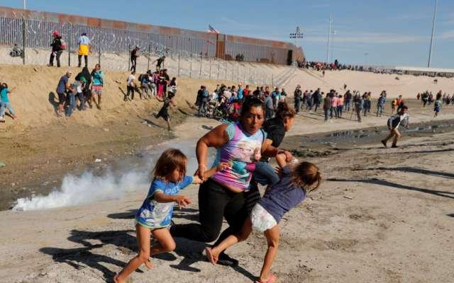 Una familia de migrantes, parte de una caravana de miles de personas que viajan desde América Central hacia Estados Unidos, huyen de gases lacrimógenos frente al muro fronterizo entre los Estados Unidos y México en Tijuana. REUTERS / Kim Kyung-Hoon