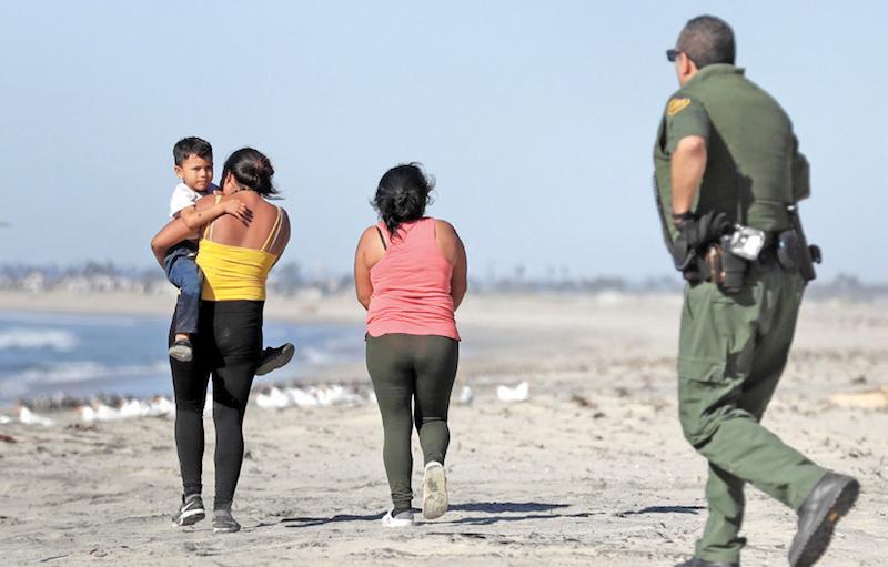 Dos mujeres y un niño migrantes son perseguidos por policías de EU, tras cruzar ilegalmente. (AP Photo/Gregory Bull)