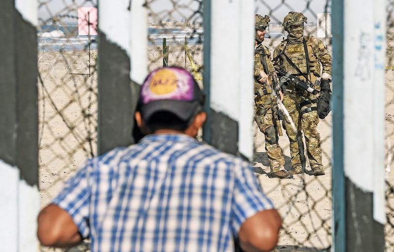 Un migrante mira a través de la cerca, frente a sol- dados de EU armados. Foto: AFP