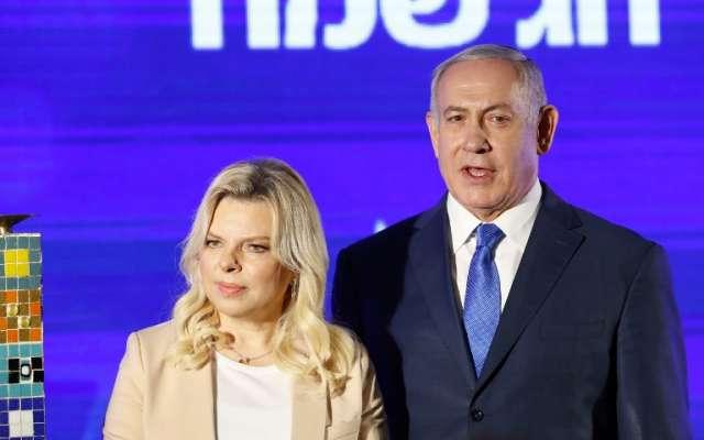 El primer ministro israelí, Benjamin Netanyahu (R), apoya a su esposa Sara antes de encender una menorah estilizada durante el inicio de Hanukkah, el festival judío de luces, en Ramat Gan. Foto: AFP