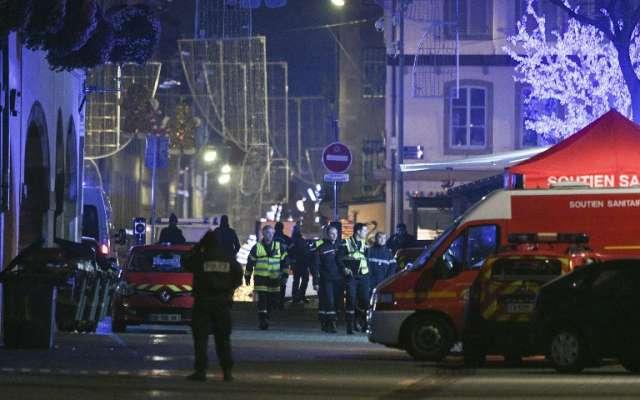 Policías y vehículos de respuesta médica de emergencia se ven en la calle de  Grandes Arcades en Estrasburgo, al este de Francia, después de un brote de disparos. Foto: AFP.