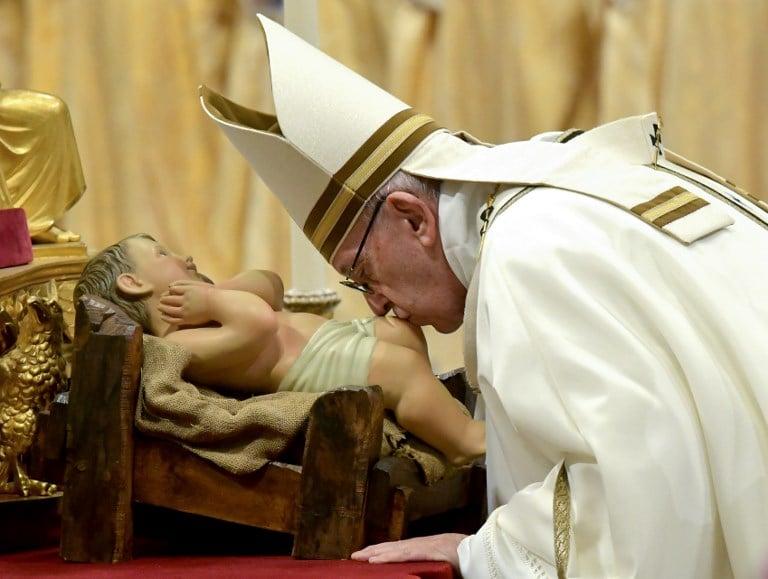 El Papa Francisco besa una figura del niño Jesús durante una misa en la víspera de Navidad en la basílica de San Pedro en el Vaticano.  Foto: AFP.