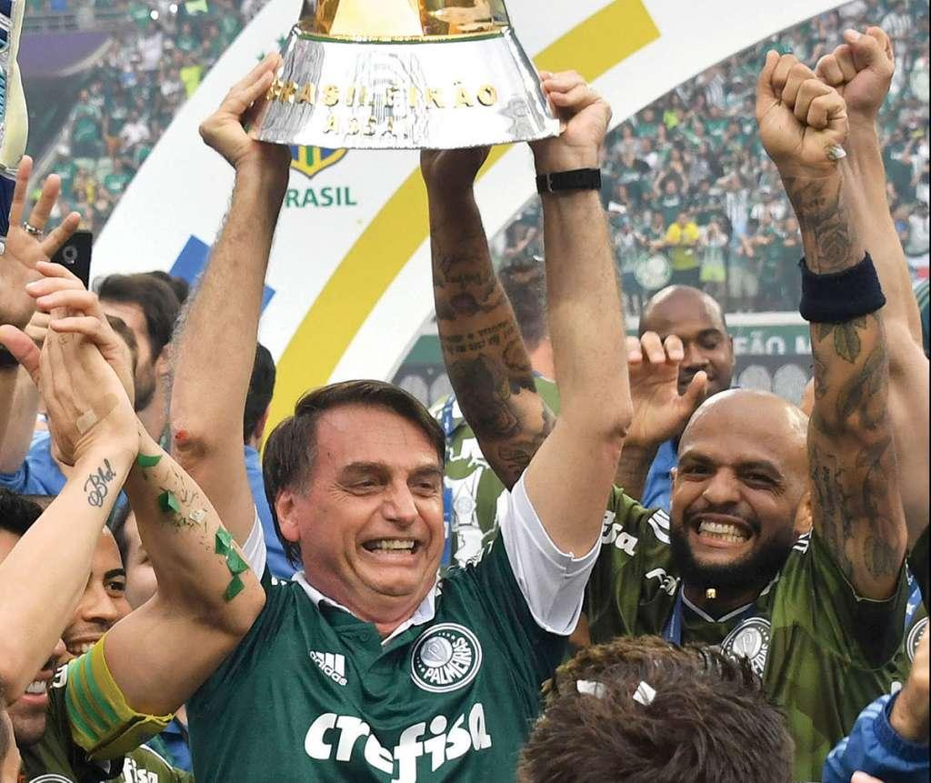 El presidente electo de Brasil, Jair Bolsonaro (C), levanta el trofeo mientras celebra con los jugadores de Palmeiras después de que el equipo ganó el campeonato brasileño, después de su partido contra Vitoria, en el estadio Allianz Parque, en Sao Paulo, Brasil, el 2 de diciembre. 2018.  Foto: AFP
