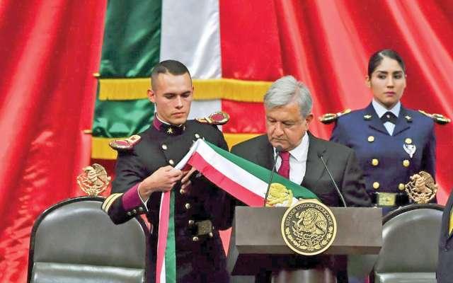 Geovanni Lizárraga, del Heroico Colegio Militar (izquierda), ayudó a colocar la banda presidencial a López Obrador. Foto: Especial.
