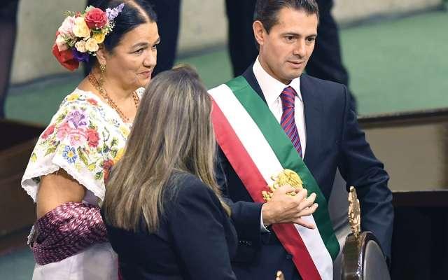 Enrique Peña Nieto con la diputada del PRI, Dulce María Sauri Riancho, antes de entregar la banda presidencial a Porfirio Muñoz Ledo, presidente de la Mesa Directiva en San Lázaro. Foto: Especial.