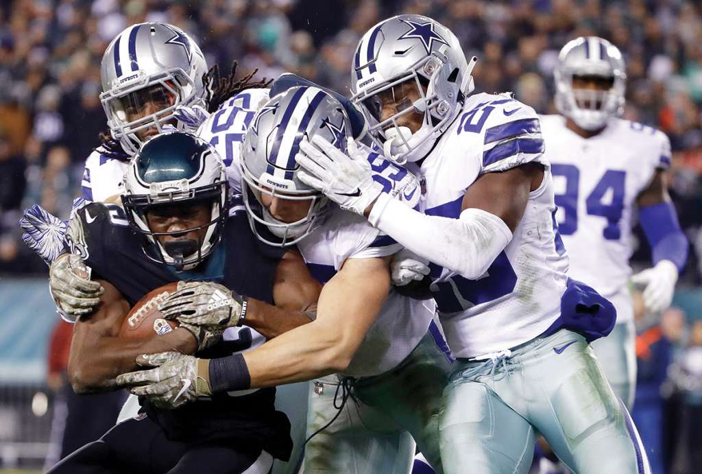 Philadelphia Eagles wide receiver Nelson Agholor, bottom left, is tackled by Dallas Cowboys middle linebacker Jaylon Smith, top left, outside linebacker Leighton Vander Esch, center, and free safety Xavier Woods during the second half of an NFL football game, Sunday, Nov. 11, 2018, in Philadelphia. (AP Photo/Matt Rourke)