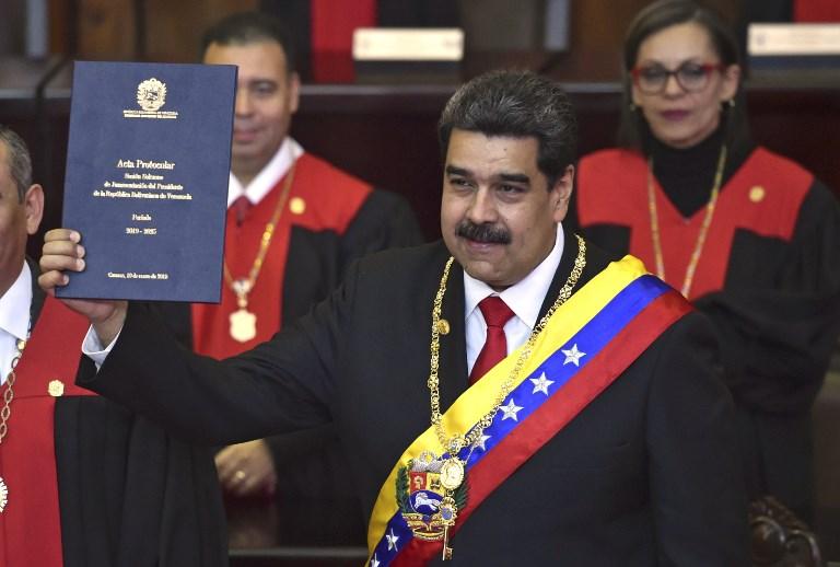 El presidente de Venezuela, Nicolás Maduro, muestra el certificado de protocolo de la ceremonia de inauguración en la sede del TSJ. Foto: AFP.