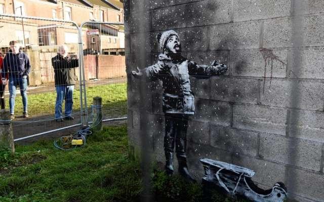 La creación abarca dos paredes, en una de ellas se muestra a un niño jugando con lo que parece ser nieve