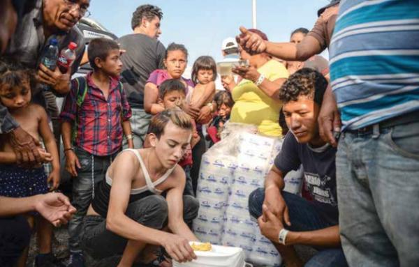 Migrantes de la caravana reparten comida en Ciudad Hidalgo, Chiapas, entre quienes hacen el trámite de ingreso a México. FOTO: EFE