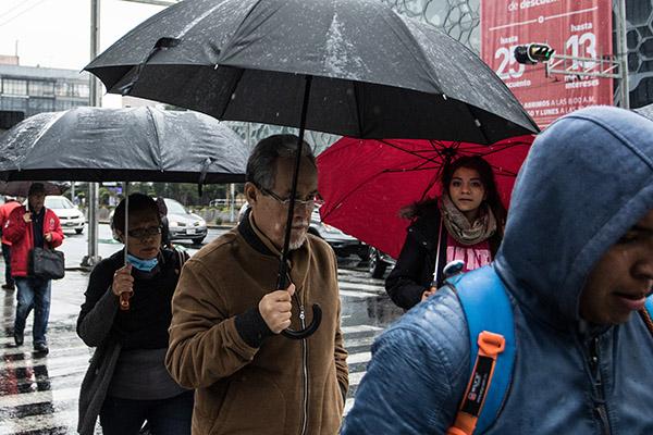 Las bajas temperaturas, acompañadas de lluvia permanente, provocaron que habitantes de la capital del país salieran abrigados y con sombrillas a realizar sus actividades cotidianas. FOTO: CUARTOSCURO