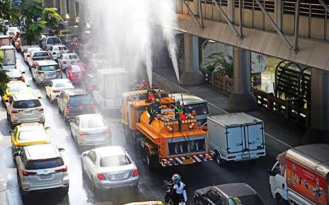 Los equipos de carreteras de Bangkok rocían agua con la esperanza de controlar el esmog.