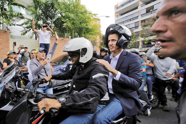 ESCAPE. Tras autoproclamarse, Juan Guaidó viajó en moto a la embajada de Colombia. Foto: AP