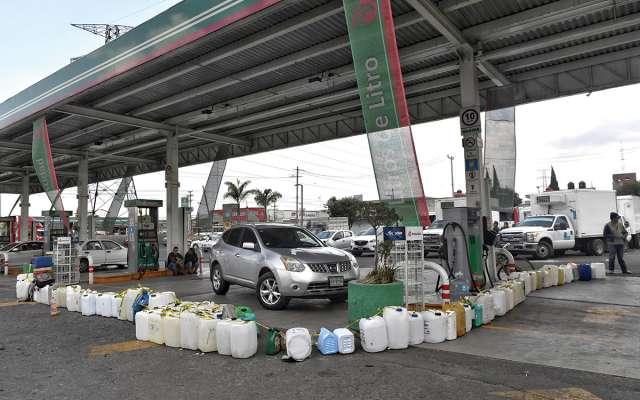 Usuarios hacen filas con bidones en una gasolinera de Toluca.