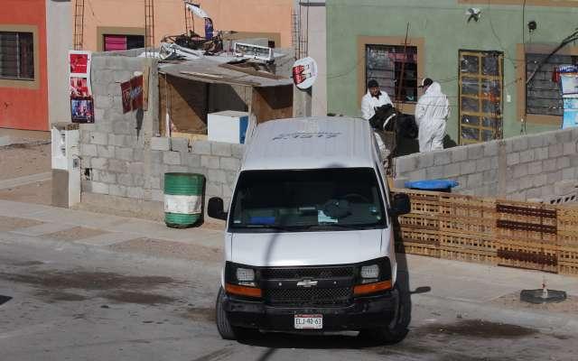 Peritos forenses trabajan en la vivienda donde fueron asesinados cinco integrantes de una familia.
