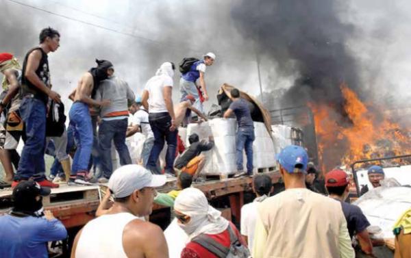 Militares incendiaron tres camiones; voluntarios intentaron rescatar la ayuda. FOTO: REUTERS
