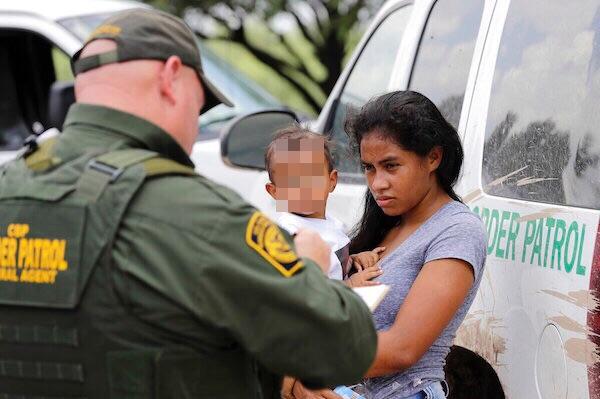 Una madre que migra de Honduras sostiene en sus brazos a su hijo de 1 año ante los agentes de la Patrulla Fronteriza de los luego de cruzar ilegalmente la frontera cerca de McAllen, Texas. Foto: AP