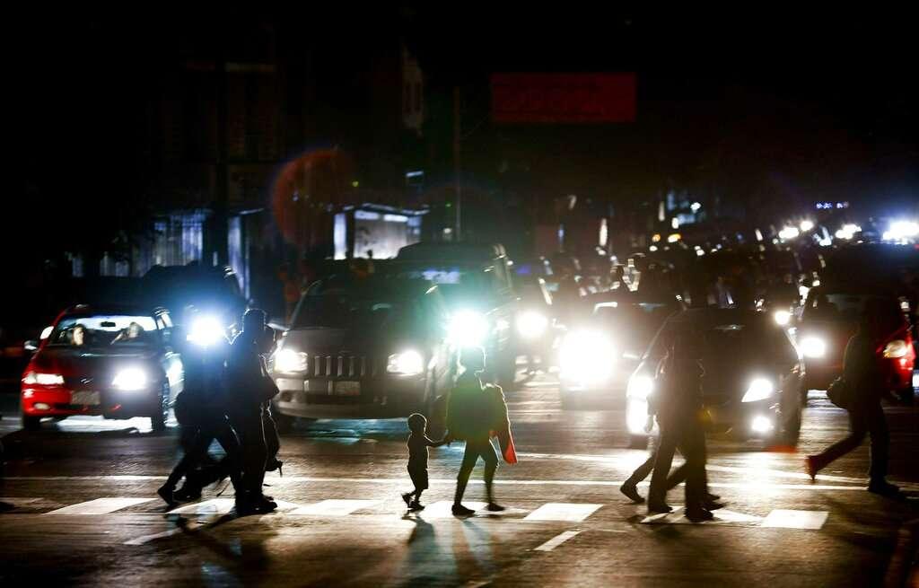 Residentes cruzan una calle de Caracas en la oscuridad tras el apagón  que inició este jueves. Foto: AP