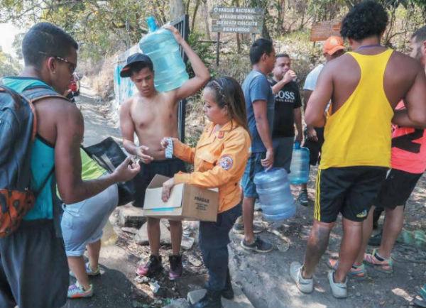 Protección Civil entregó pastillas potabilizadoras a personas que llenan recipientes de agua en una canaleta.FOTO: ESPECIAL