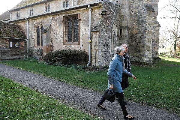 CRISIS. La premier May se retira con su esposo después de asistir a un servicio religioso. Foto: AFP