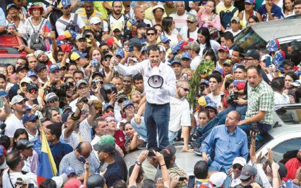 Juan Guaidó subió a un automóvil; la policía impidió que se instalara su templete en Caracas. FOTO: AFP
