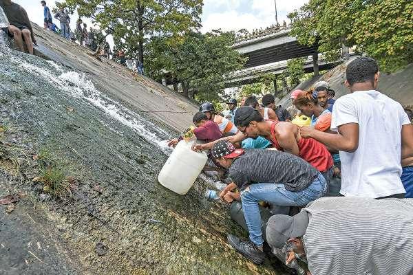 DESESPERACIÓN. Ante la escasez, decenas de personas buscan agua en el río Guaire, en Caracas. Foto: AFP