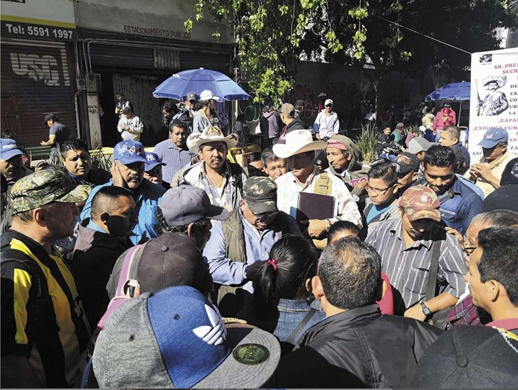 Uno de los dirigentes (gorra y camisa azul) dio dinero a los campesinos que aceptaron plantarse en las instalaciones de Sedatu.FOTO: ESPECIAL