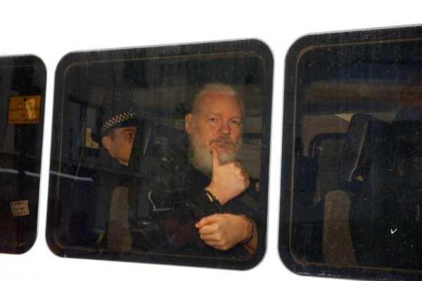 Fotógrafos y periodistas rodearon el vehículo de seguridad donde iba Julian para capturar las primeras imágenes. Foto: Reuters