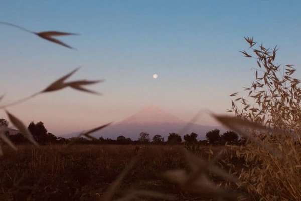 El Volcán Popocatépetl con la Luna rosa sobre él.FOTO: ESPECIAL