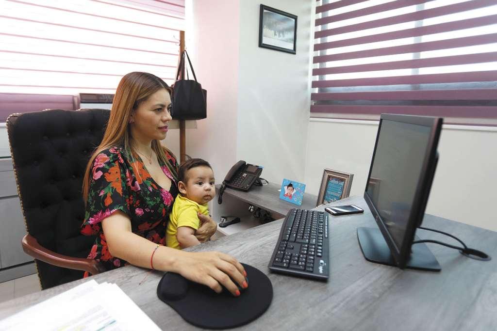 Desde su oficina en la Secretaría del Trabajo local, Soledad Aragón sujeta a su bebé para cuidarlo.FOTO: NAYELI CRUZ