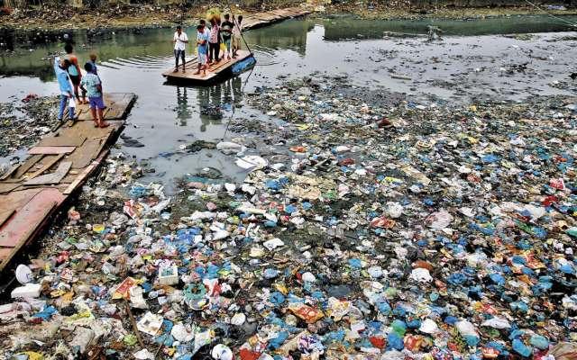 Un hombre guía una balsa a través de un canal contaminado lleno de bolsas de plástico.FOTO: AP