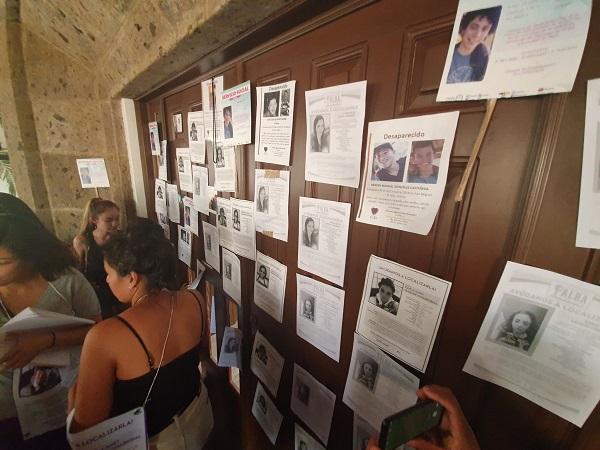 Al no recibir respuesta a su petición, pintaron consignas en el exterior de la fachada en Casa Jalisco, mientras otras personas golpeaban y rompían la madera en la puerta principal. Foto: Especial