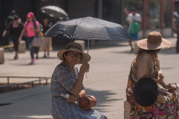 Personas se cubren del sol